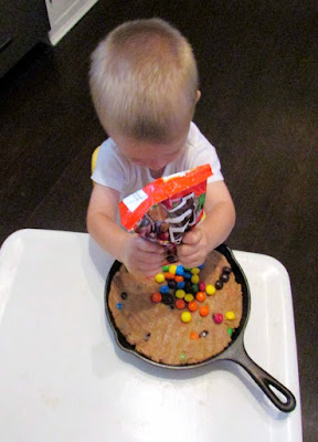 Little dude pouring extra m&ms on top of skillet cookie