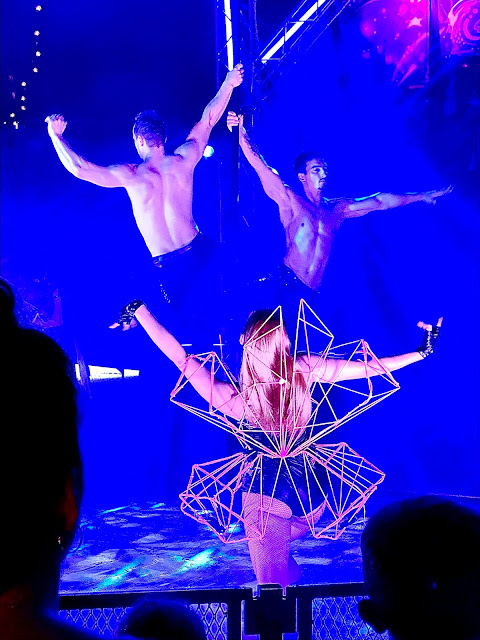 two men on an aerial pole with a dancer in the foreground
