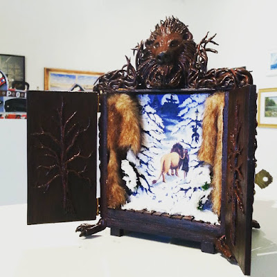 Small wooden cupboard decorated with Narnia-themed items, on display in an art gallery.