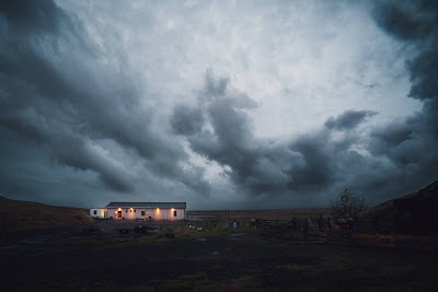 A low and long white house, lighted from inside. It sits on a hill with storm clouds bearing down. Photo by Dorin Vancea on Unsplash.