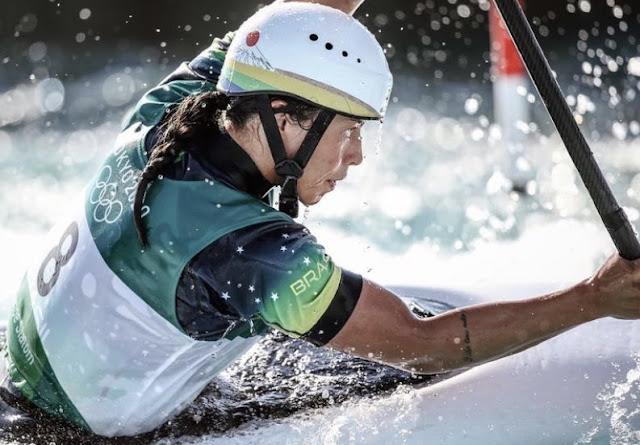 Ana olha compenetrada para um dos portões. Ela usa capacete branco com detalhes na cor da bandeira brasileira, camisa verde e colete branco com o número 8.