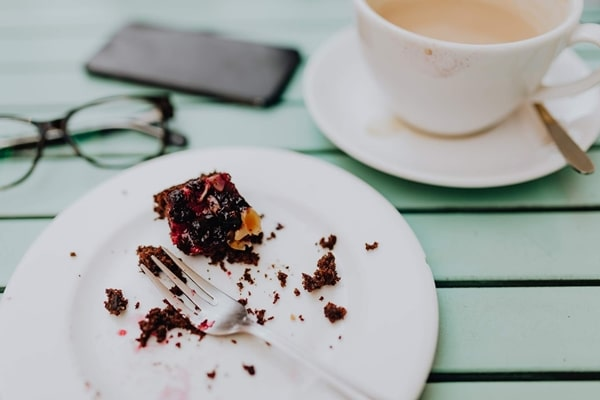 Mesa de café, com uma xícara e uma sobremesa inacabada