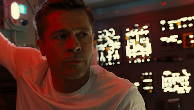 Brad Pitt sits in a spaceship wearing a white shirt questioning life in a movie still for the 2019 sci-fi drama As Astra