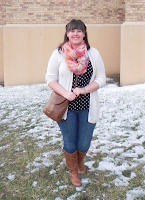 an outfit with a black polka dot top, a white cardigan, a floral scarf, jeans, and boots