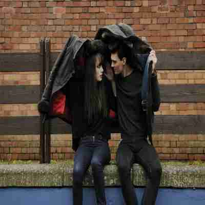 gf and bf using a coat as an umbrella