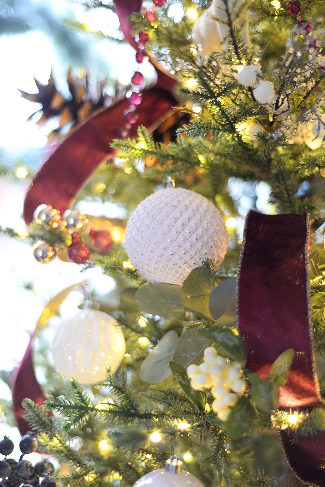 Living room decorated for Christmas with red and white Christmas tree. Canadian Tire mulberry collection Christmas ornaments. Rose gold christmas decorations