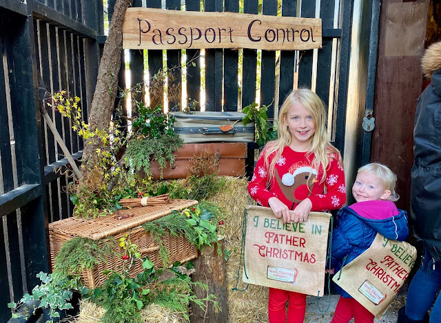 "A christmas foliage display, a sign saying passport control and 2 children with special backpacks saying ""I believe in Father christmas"""