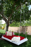 A daybed hanging in the shade of a tree.