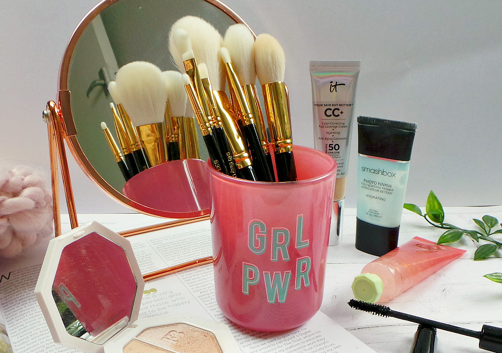 black and gold makeup brushes in a pink jar that says grl pwr on it in front of a mirror. There are various makeup products and a magazine on the surface.