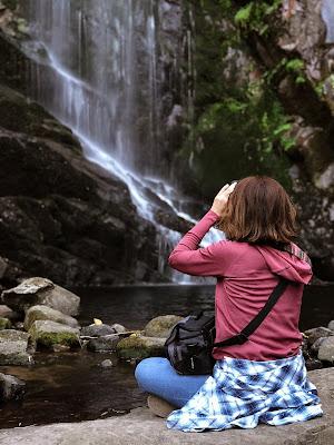 Mujer sentada de espaldas fotografiando una cascada