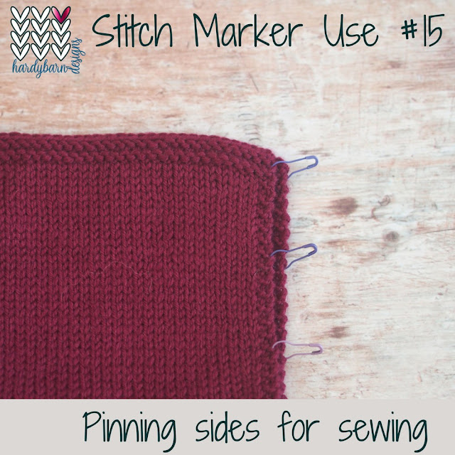 Two pieces of burgundy knitting attached with stitch markers down one edge