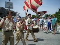 men marching in 4th of July parade, dressed in colonial clothes