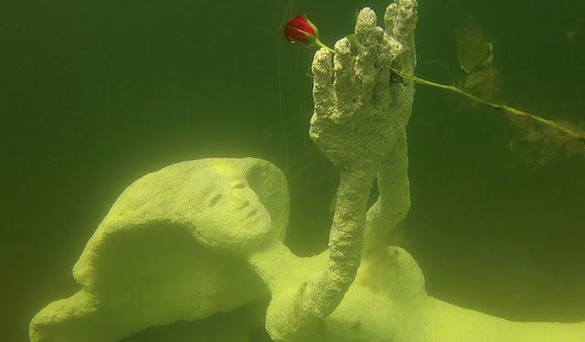 Betonipatsas veden alla: nainen makaa selällään ja pitelee kukkaa päänsä päälle nostetuilla käsillä