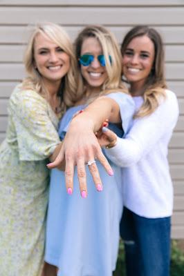 Novia enseñando su anillo de compromiso con amigas a los lados