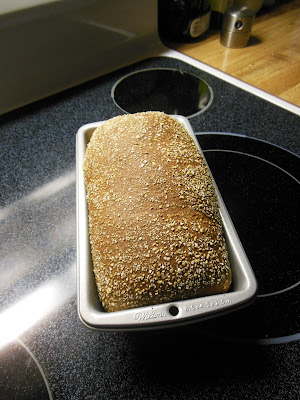 A single loaf of whole grain bread, with honey and oats.