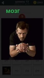 Мужчина  держит модель мозга, наклонившись вперед на вытянутых руках и глядя перед собой