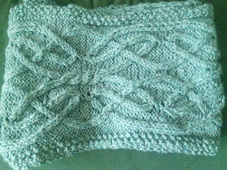 a bulky-weight scarf with a Celtic knot style cable.  Scarf is folded up with the ends tucked underneath.
