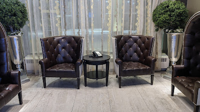 Two leather chairs side by side with a small wooden table in between. There is a land line phone on the table.