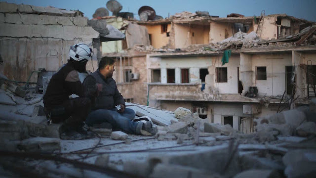 Tras el rescate de víctimas en un bombardeo, dos voluntarios de Defensa Civil Siria miran la ciudad devastada