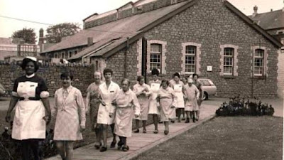 A photograph showing a group of nurses and patients walking outside Ely. 'outside of Ely Hospital' The Peoples Collection- copyright Mona Hussey.