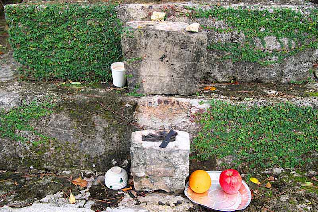 Incense and offerings at stone monument