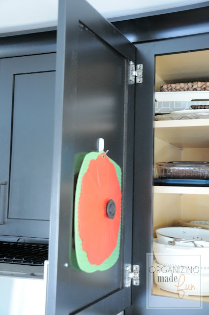 Use wired command hooks to hold rubber lids for serving dishes on back of cabinet door :: OrganizingMadeFun.com