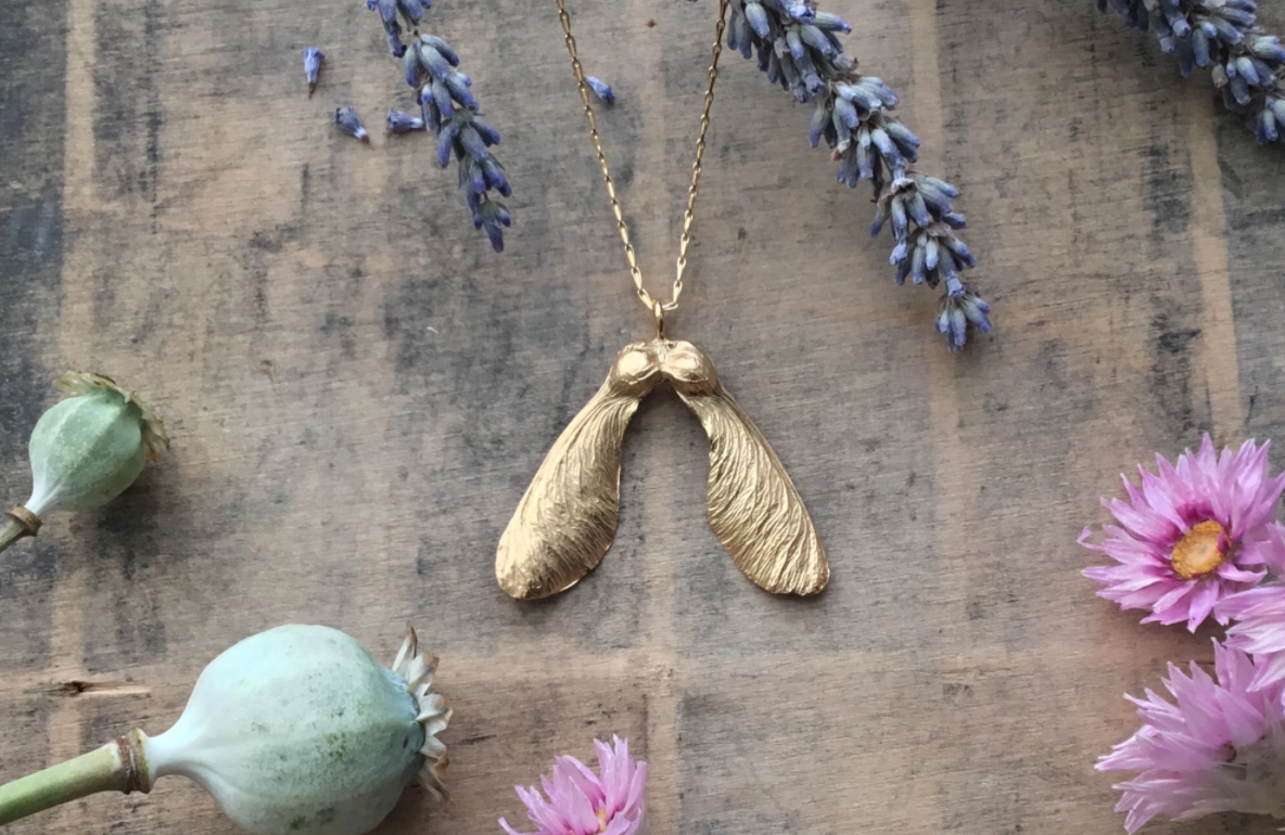 A gold sycamore seed necklace
