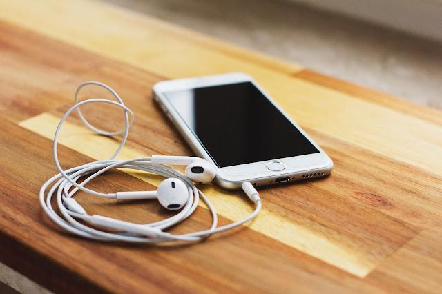 Celular iPhone com fones em cima de uma mesa de madeira