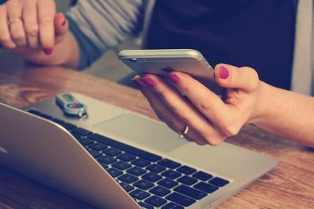 mulher segurando celular e digitando no computador