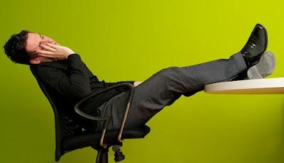 hombre sentado y durmiendo en la silla frente a su escritorio