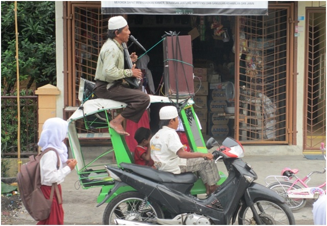Seorang pekerja seni jalanan memanfaatkan sepeda motor dan memodifikasinya sedemikian rupa sehingga menjadi becak serbaguna