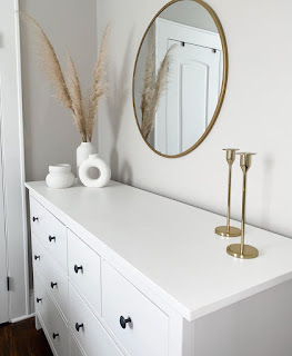 trio of modern white vases with dried grasses set atop white bedroom dresser