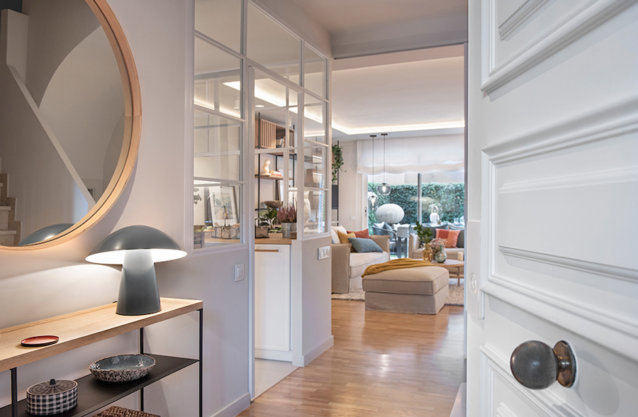 Recibidor, salón y  cocina detrás de pared con cuarterones de cristal.