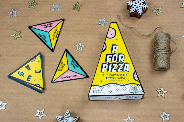 A wedge shaped cardboard box for the P for Pizza game, next to some triangular shaped pieces. On one side they have 3 letters and on the other 3 categories
