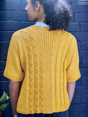 Photo of a model wearing a yellow knitted cardigan with the back centre panel showing