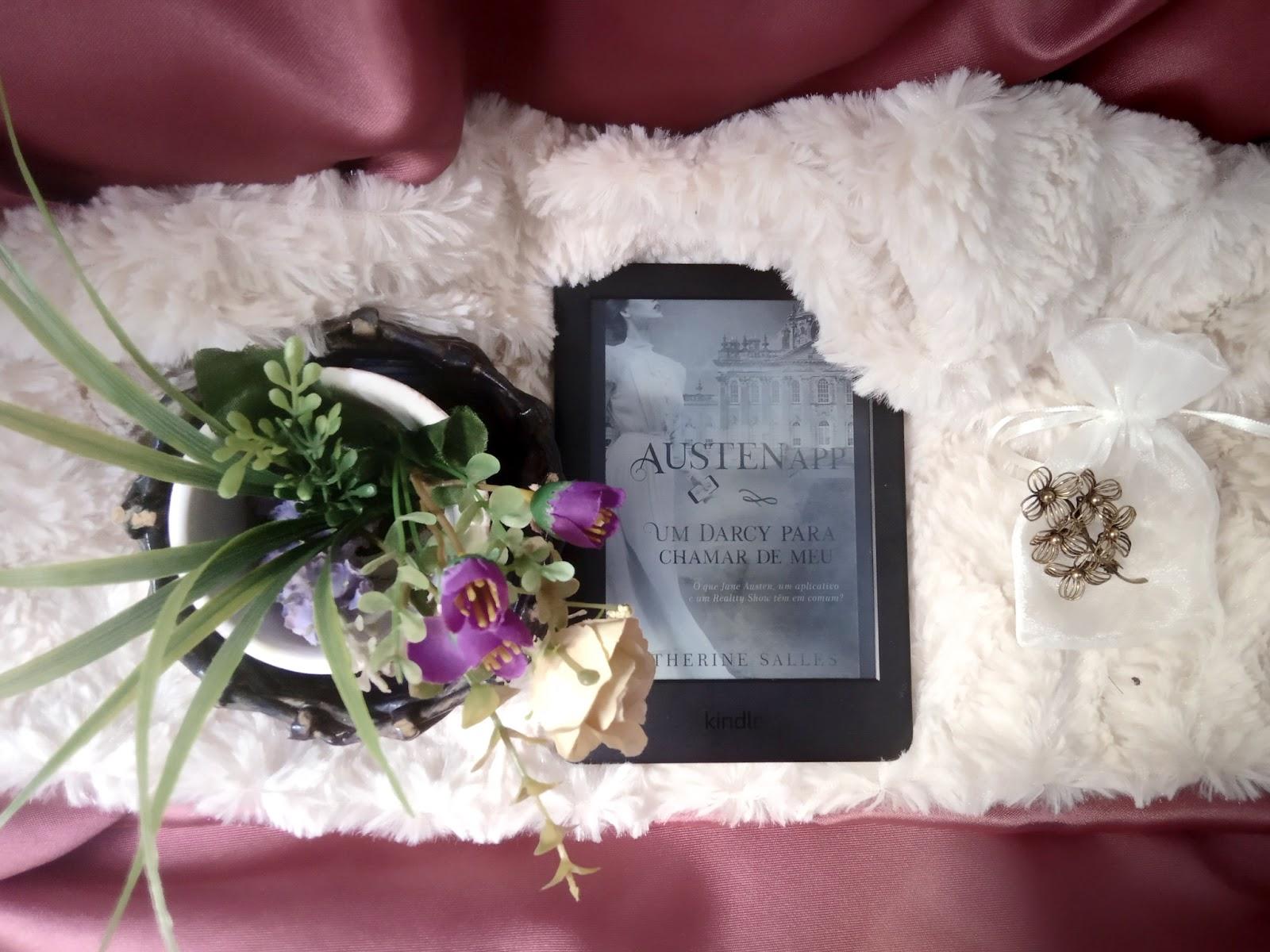 Foto com fundo mesclado, um tecido liso vermelho vinho, sobreposto por uma manta peluda branca, em cima ha um aparelho kindle ao centro com a capa de AustenApp, um vaso de flores ao lado e do outro lado um saquinho transparente de tecido com um broche em formato de flor em cima