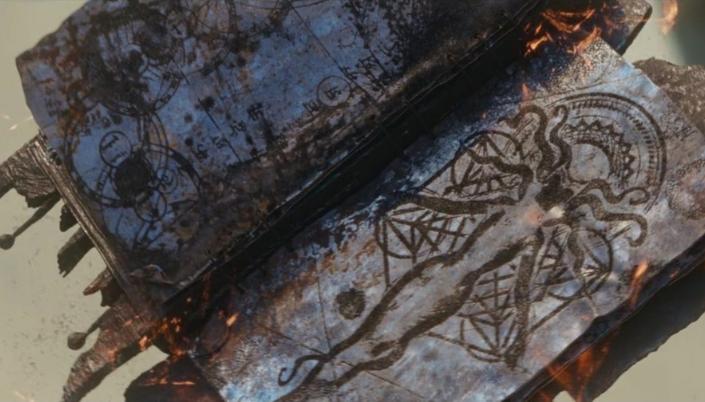 Imagem: o livro Darkhold, um grimório de magia feito de páginas de aparência metálica e escura que brilha levemente uma cor alaranjada e contém ilustrações de círculos, runas e uma ilustração de uma figura que lembra a Feiticeira Escarlate, uma silhueta feminina com uma tiara em formato de M ao redor da cabeça e uma capa.