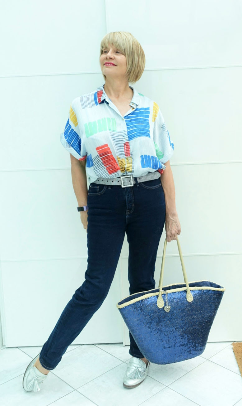 Casual fashion for the over 40s.  Blue jeans with abstract patterned top, silver loafers and blue sequinned straw bag.
