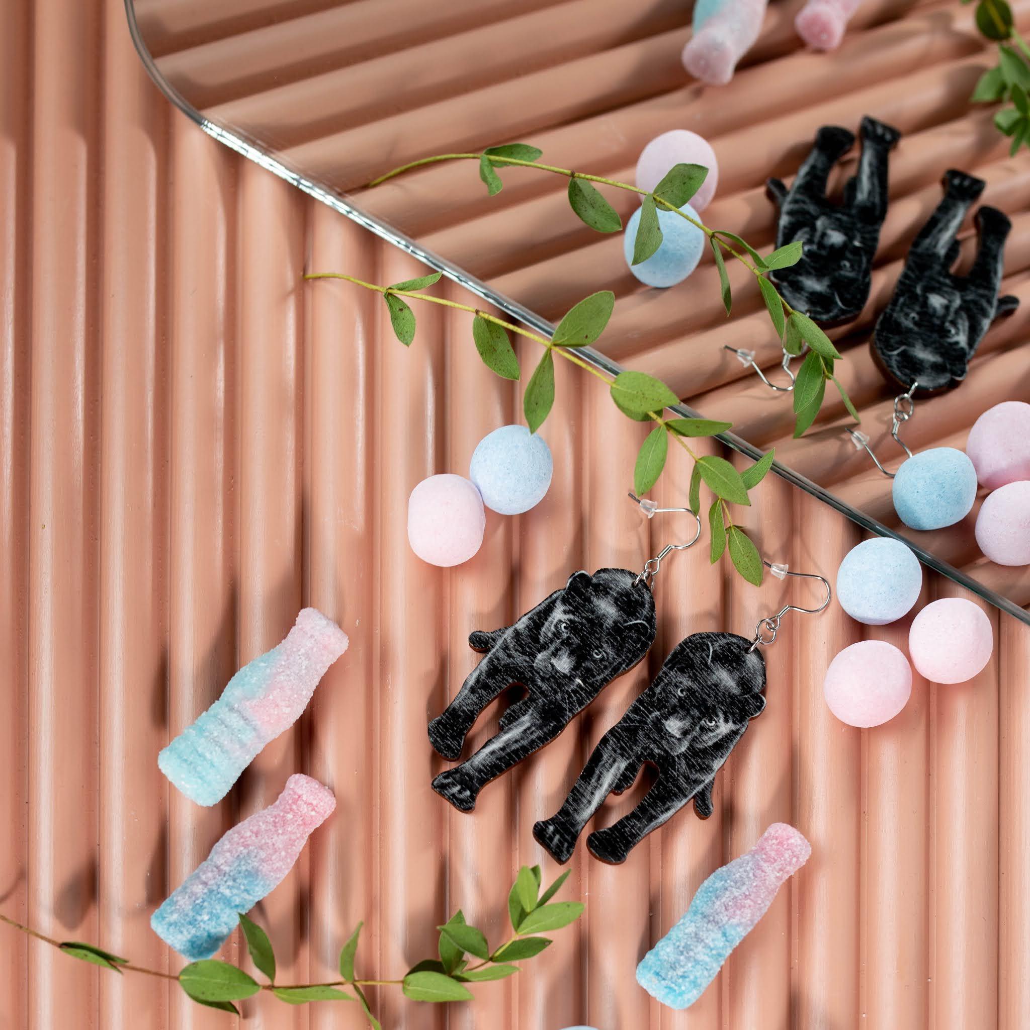 Vaaleanpunaisen sormipaneelin päällä pantteri korvakorut, irtokarkkeja, peili ja pieni lehtisiä eucalyptuksen oksia.