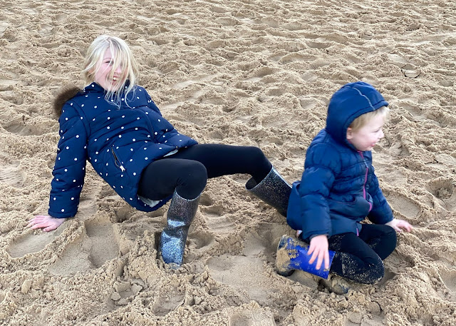 Sisters on the sand messing around and laughing in coats and wellies