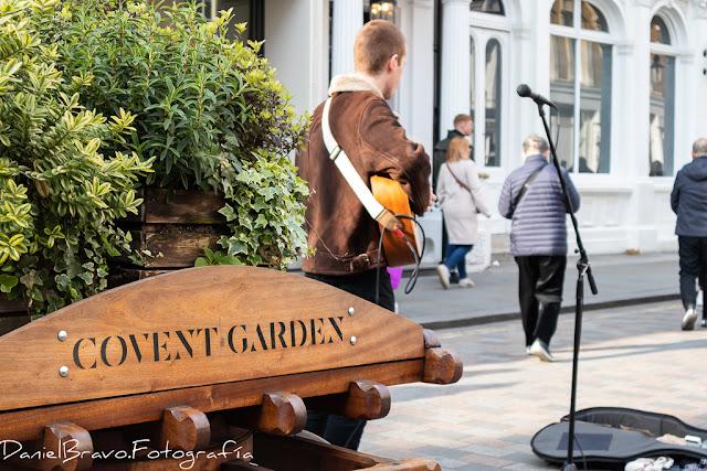 Entrada al mercadillo de Covent Garden con un músico callejero tocando la guitarra y unas flores a la izquierda.