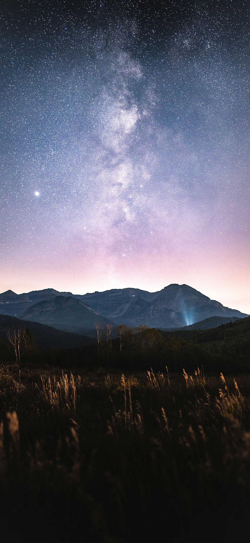 green grass field near mountain under starry night wallpaper