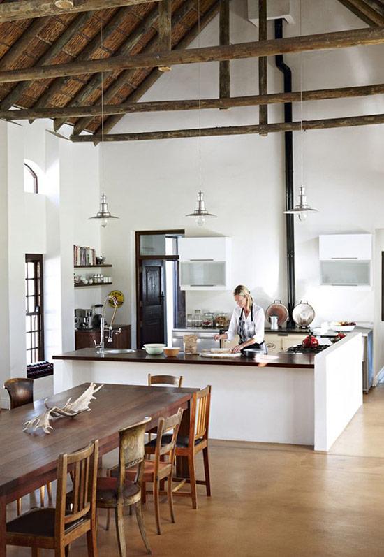 Phòng bếp theo phong cách trang trại hiện đại với một lò sưởi và không gian phòng ăn mộc mạc với những chiếc ghế khác nhau.