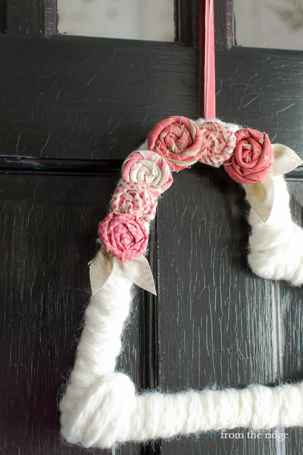 yarn wreath with flowers made from fabric scraps
