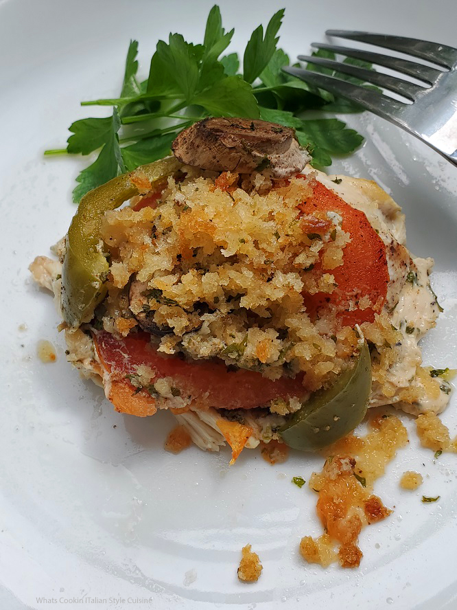 this is chicken topped with tomatoes, peppers and mushrooms on a white plate