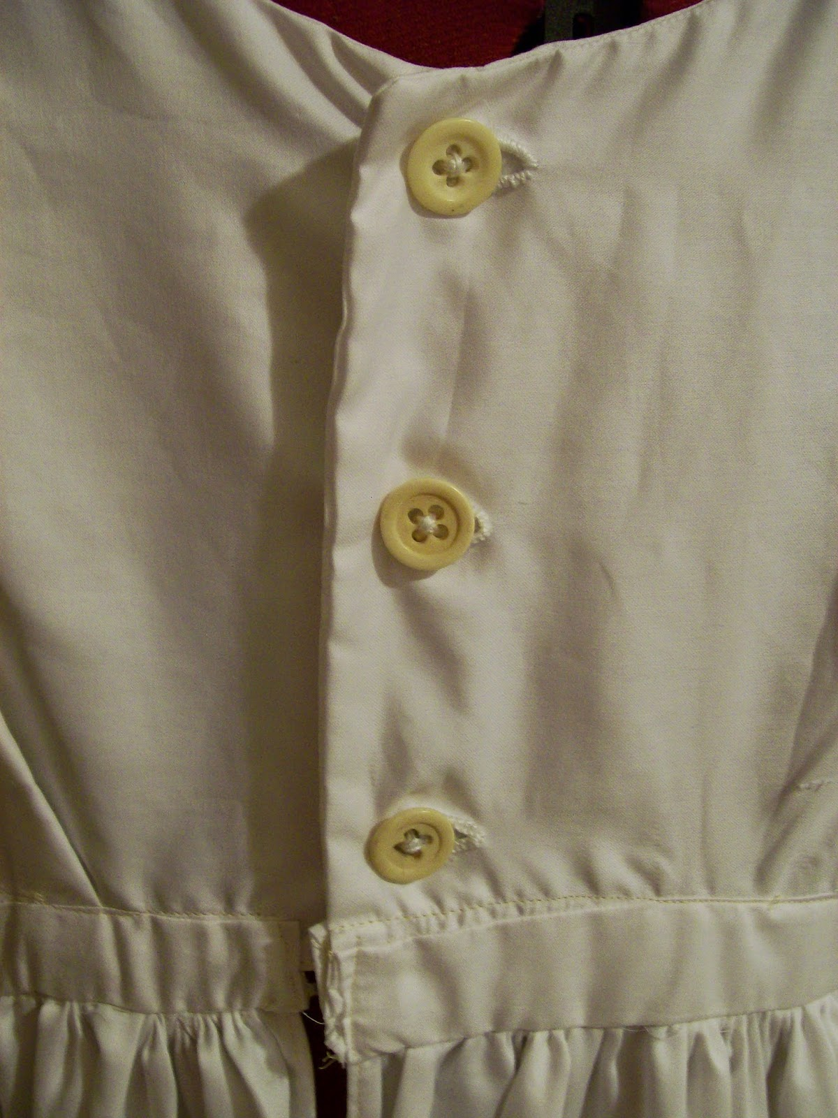 Buttons down the back of the petticoat bodice.