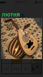 На ковре лежит музыкальный инструмент под названием лютня