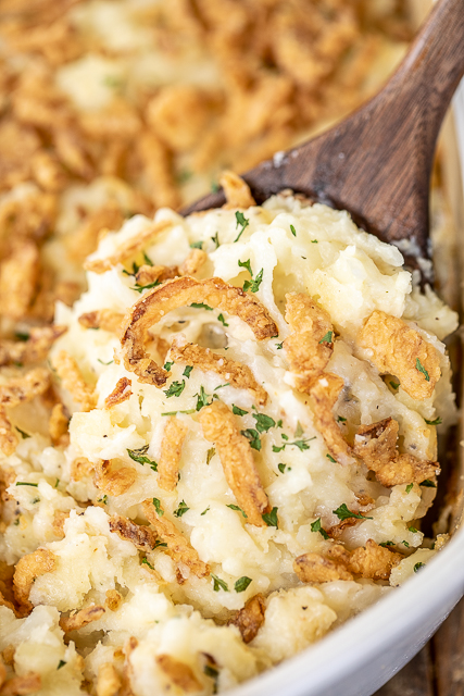 scooping mashed potatoes from casserole dish