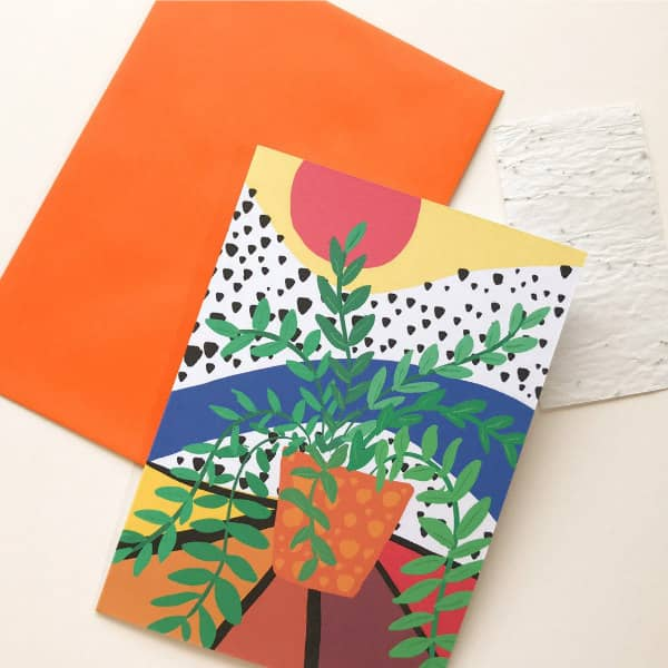 colorful printed card with paper cut greenery in flower pot and envelope