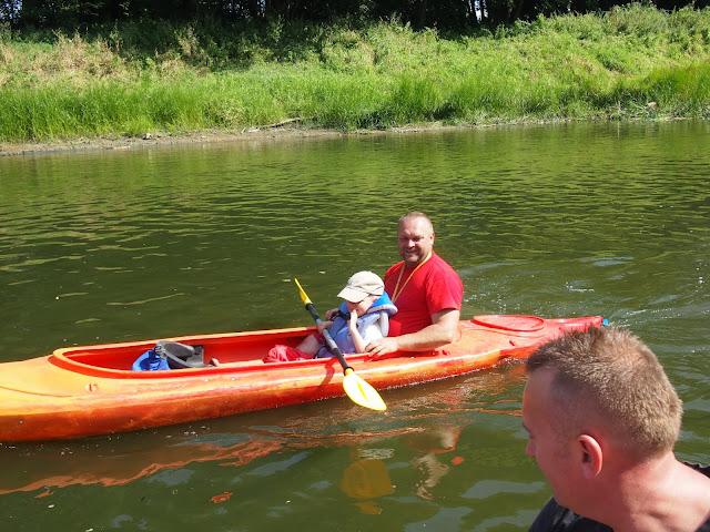 Tata płynie po Warcie kajakiem polietylenowym z małym dzieckiem.